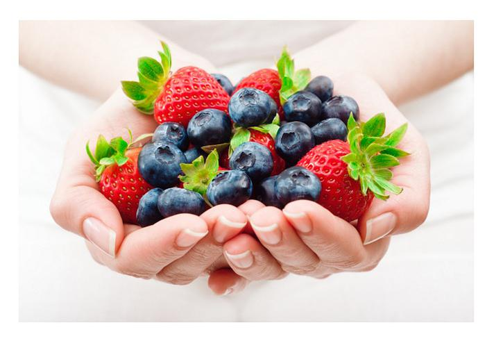 Nutrition and a healthy diet for weight loss: hands holding blueberries and strawberries