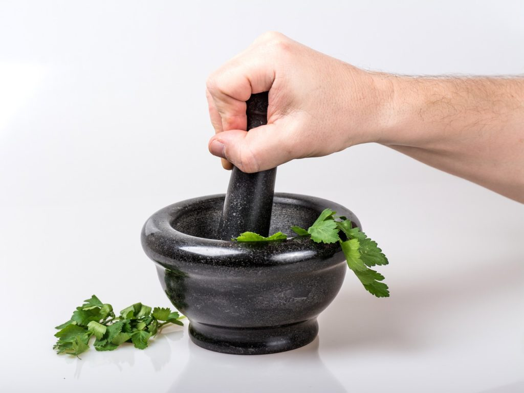 green herbs ground by mortar and pestle