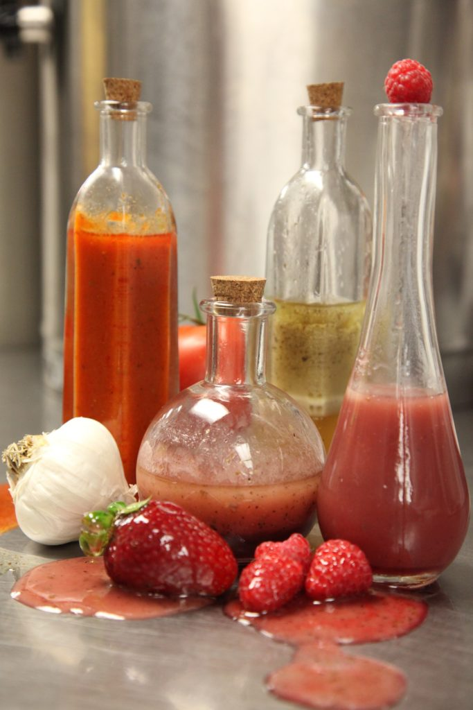 salad oils in bottles with corks, berries, garlic