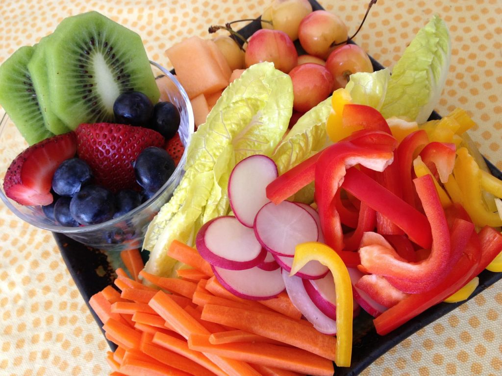 healthy food platter: cut up kiwi fruit, strawberries, blueberries, cantaloupe, cherries, lettuce, carrots, radishes, red bell pepper, yellow bell pepper